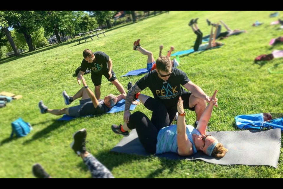 Brandon Peacock provides tips to a person doing yoga at the park this summer. Peacock started Peak Performance and has grown the local business with the help of the CDC. Contributed photo