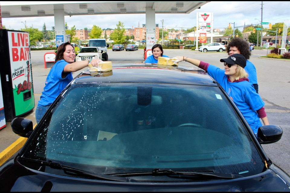 Georgian College students wash a car Wednesday at the Canadian Tire Gas Bar in Orillia during the annual Shinerama fundraiser. Nathan Taylor/OrilliaMatters