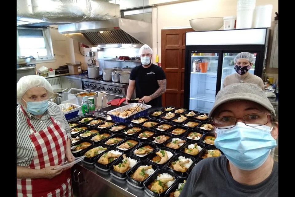 Volunteers from The Sharing Place Food Centre are shown preparing meals in the St. James' Anglican Church kitchen.