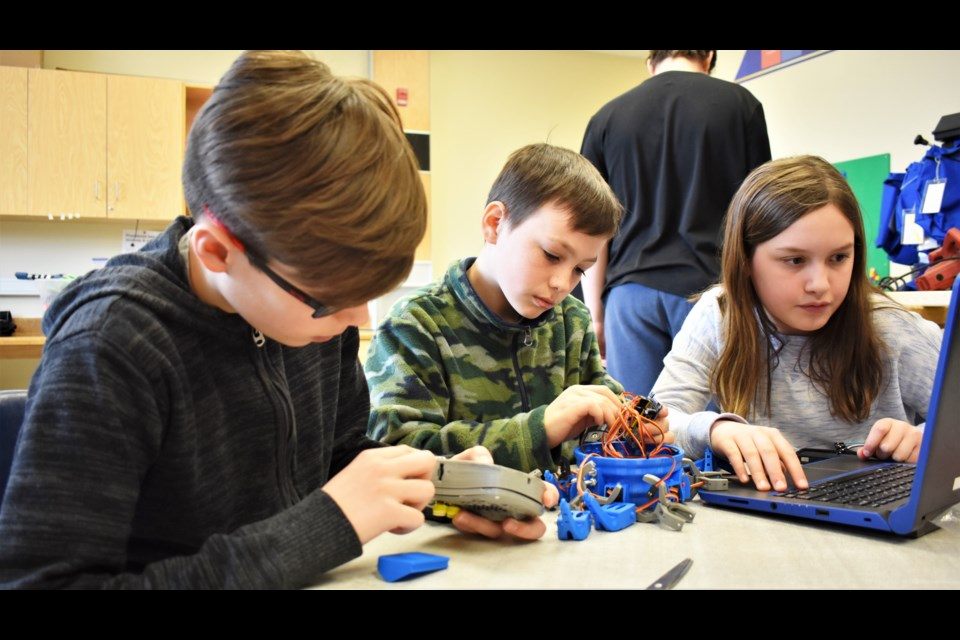 Grade 5 students, from left, Aidan Granulo, Aidan Sedore and Ava Cassar work on a robot they are building. They used the lab's 3D printer to create a case and game pad and are busy assembling the mechanics and electronics. Dave Dawson/OrilliaMatters