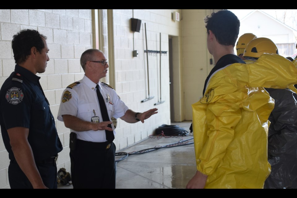 Orillia Deputy Fire Chief Jeff Kirk, centre, provides some advice and feedback to a pair of Patrick Fogarty students who endured what it was like to be washed after being exposed to dangerous chemicals as part of a drill in 2018. Dave Dawson/OrilliaMatters File Photo