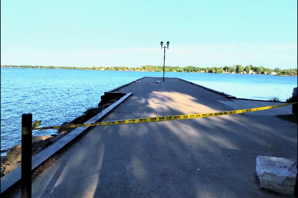 The government dock at Couchiching Beach Park was taped off Saturday while police investigated after a man was pulled from the water without vital signs.