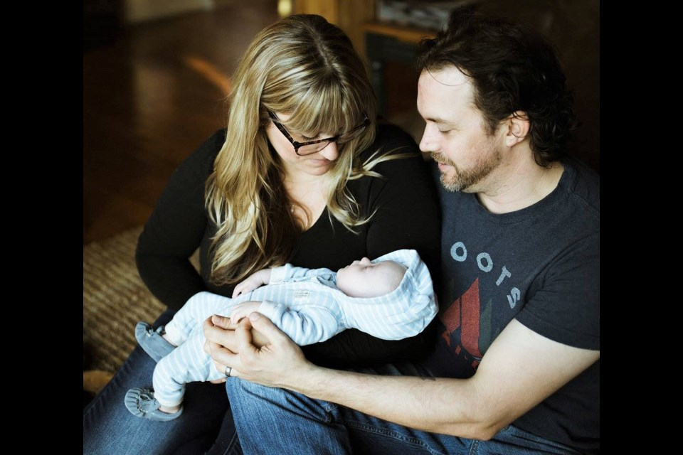 Sarah-Valiquette Thompson and husband, Ian Thompson, share a special moment with their infant son, Harvey. The local family will be marking World Down Syndrome Day today by wearing crazy socks and celebrating the uniqueness of their son. (Joanna Chrichton  Photography)