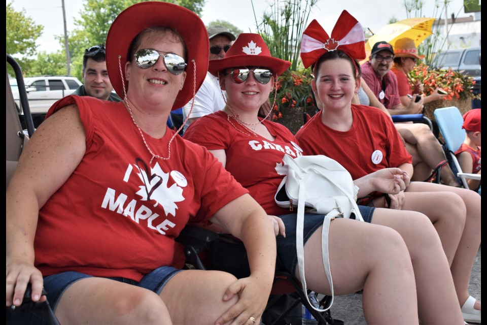 Many people selected prime places to plant their lawn chairs and enjoy the Canada Day parade on Mississaga Street Sunday. Above, from left, Amelia Martin, Mikayla Martin and Claire Martin sport their Canada colours as they wait for the parade to begin. Dave Dawson/OrilliaMatters