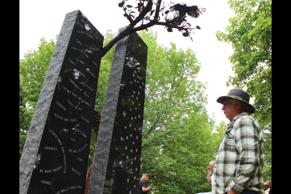 Brian Logie takes a moment of reflection Saturday as he examines the Survivors Memorial Monument that was unveiled at the Huronia Regional Centre Cemetery. Nathan Taylor/OrilliaMatters