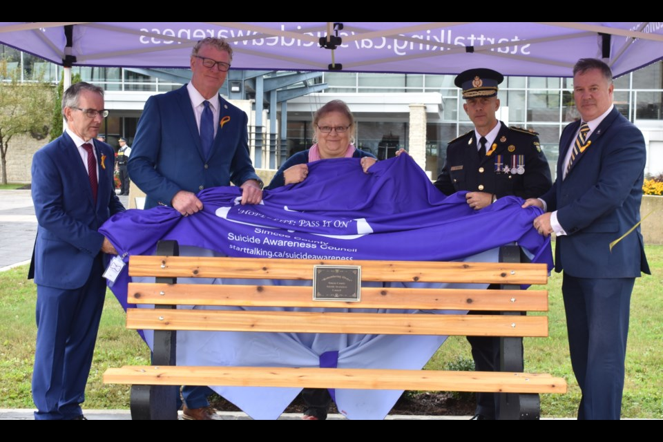 A new bench was unveiled by the Simcoe County Suicide Awareness Council and dignitaries at a special ceremony Tuesday at OPP General Headquarters. From left: Simcoe North MP Bruce Stanton, Orillia Mayor Steve Clarke, Bernadette Copeland of Simcoe County Suicide Awareness Council, OPP Commissioner Thomas Carrique and Rob Jamieson, president of the OPP Association. Dave Dawson/OrilliaMatters