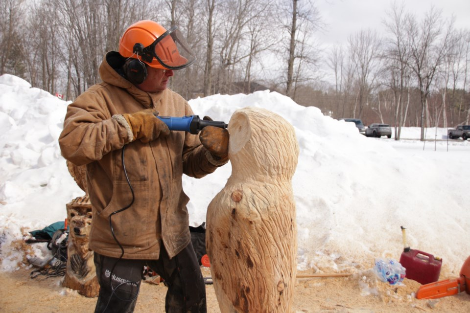 Dennis Payne, of Huntsville, works on an owl carving at the Washago Carving Event. Mehreen Shahid/OrilliaMatters