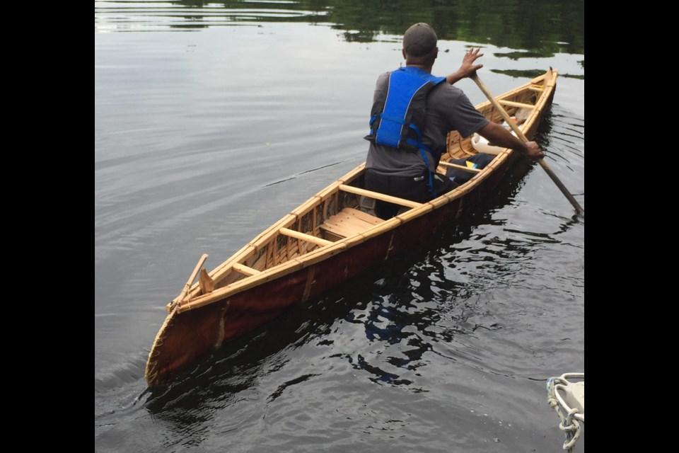 John Harrison paddles a canoe he built.