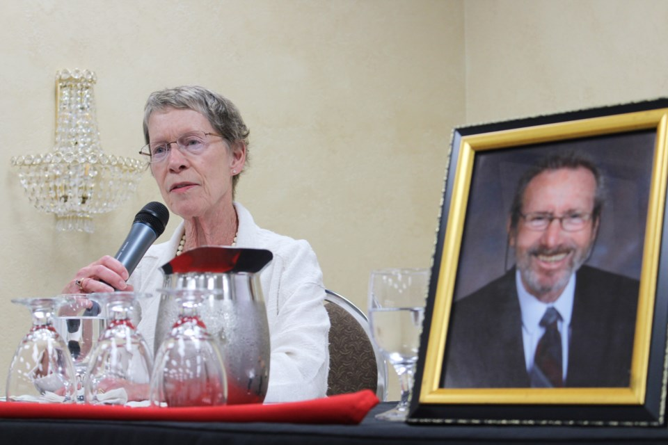 Cheryl Behan speaks Wednesday at the Best Western Plus Mariposa Inn and Conference Centre, where she shared the story of her husband, John Davey (shown in the photograph beside her), who chose a medically assisted death. Nathan Taylor/OrilliaMatters