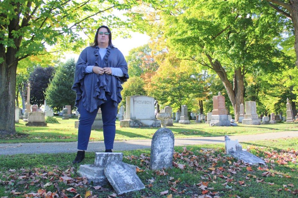 Stephanie Worthington, business manager at St. Andrew's-St. James' Cemetery in Orillia, stands next to some of the older headstones that were damaged sometime between Friday afternoon and Monday morning. Nathan Taylor/OrilliaMatters