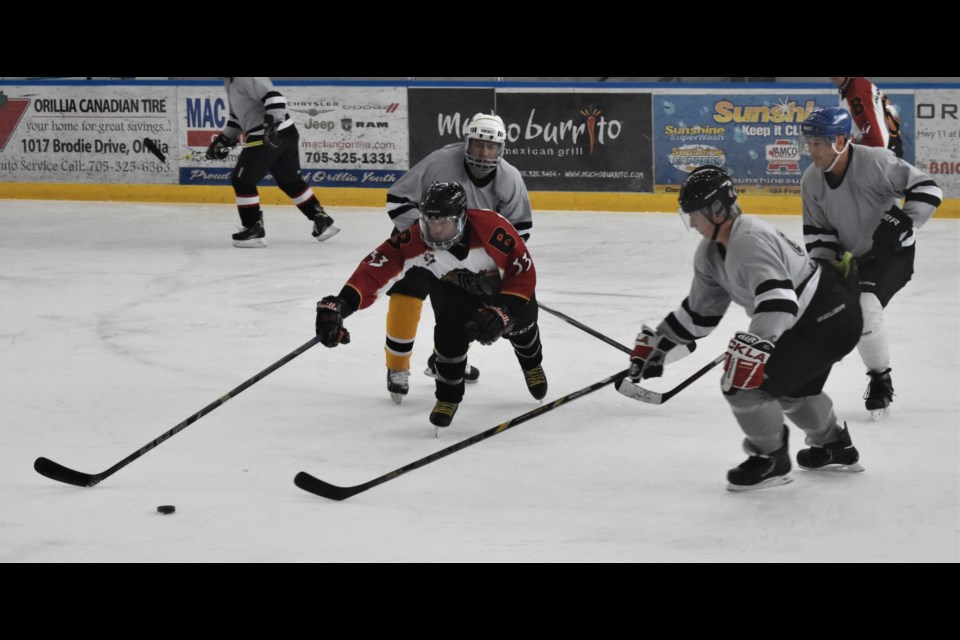 Rivals battle for control of the puck during action Saturday at the Brewery Bay Oldtimers and Big Brothers Big Sisters Hockey Tournament. Dave Dawson/OrilliaMatters