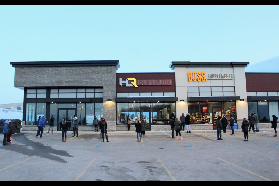 People line up to enter BOSS Supplements in Orillia during a demonstration Wednesday.