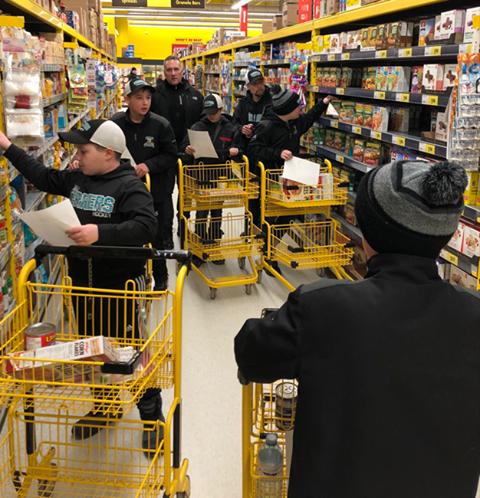 Members of the Orillia Terriers minor peewee AE team use teamwork to help those less fortunate.