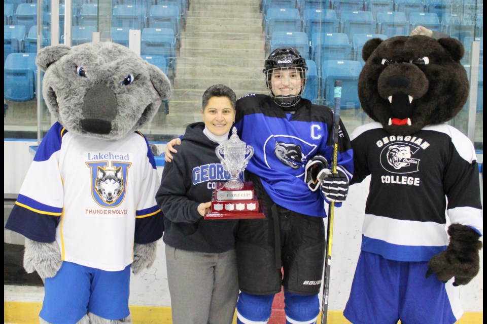 Stephanie Dimech, dean of Georgian College's Orillia campus, presents the Frost Cup to Grizzlies captain Clara Hall after Thursday's game at Rotary Place. Nathan Taylor/OrilliaMatters