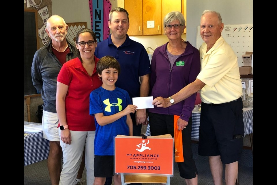 Joan Davidson and Harold Graham (far right) are presented their prize for winning the Mr. Appliance Lawn Bowling event by David, Leni and Jason Francey from Mr. Appliance. Draw master Rick Swinton is shown on the left.