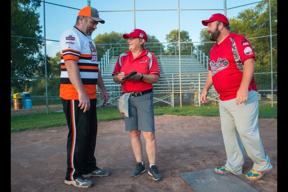 Pam Mogridge, the umpire-in-chief for Orillia Slo-Pitch, exchanges lineup cards with coaches from two local teams during a recent game. Tyler Evans/OrilliaMatters