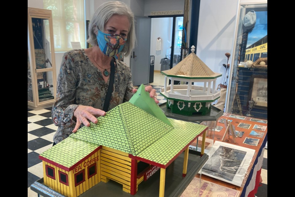 Sheila Davis, an Orillia Museum of Art and History volunteer, examines a model of Frenchs, a waterfront landmark. Davis and volunteer Bruce Jones have put together Summer in Orillia, an exhibit that will continue through September. Sam Gillett/OrilliaMatters