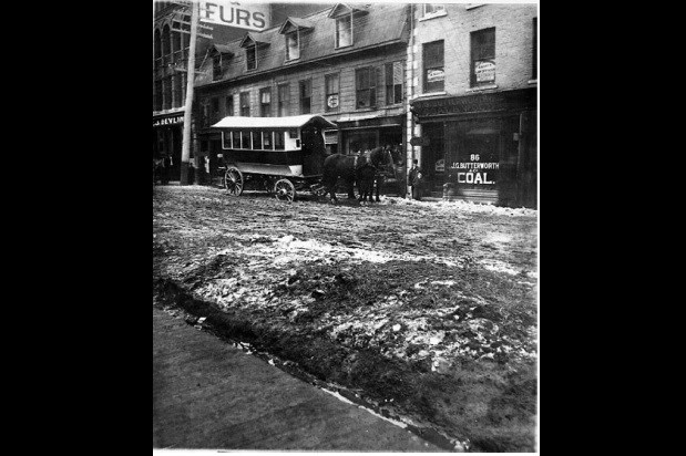Sparks Street between Metcalfe and Elgin Streets, c. 1877, photographer unknown.  Notice the wooden sidewalk set lower than the roadway. City of Ottawa Archives, CA-001504.