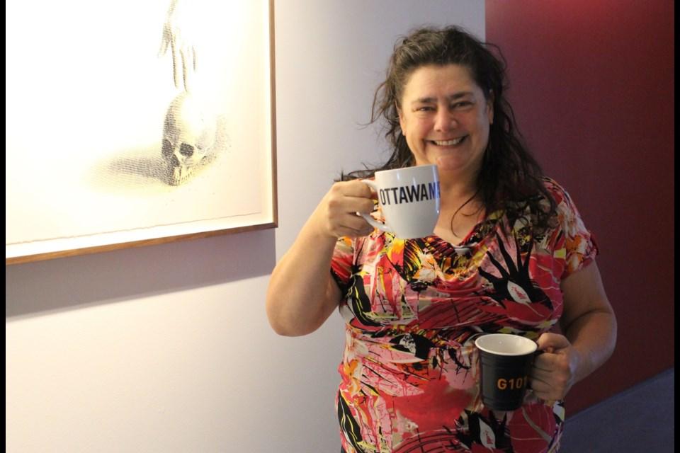 Laura Margita, Director and Curator of Gallery 101, in front of Lee Henderson's work