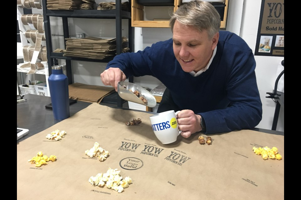 Michael Sinclair, Co-Owner of YOW Popcorn Co., showing off different flavours of his gourmet popcorn. (Andrew Pinsent/Ottawa Matters.com)