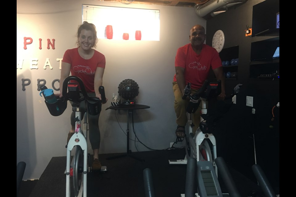 Vivek Kumar and Celine Filion are picture on bikes at Moffat Farm Cycling Club, their spin class created for charity. (Andrew Pinsent/OttawaMatters.com)