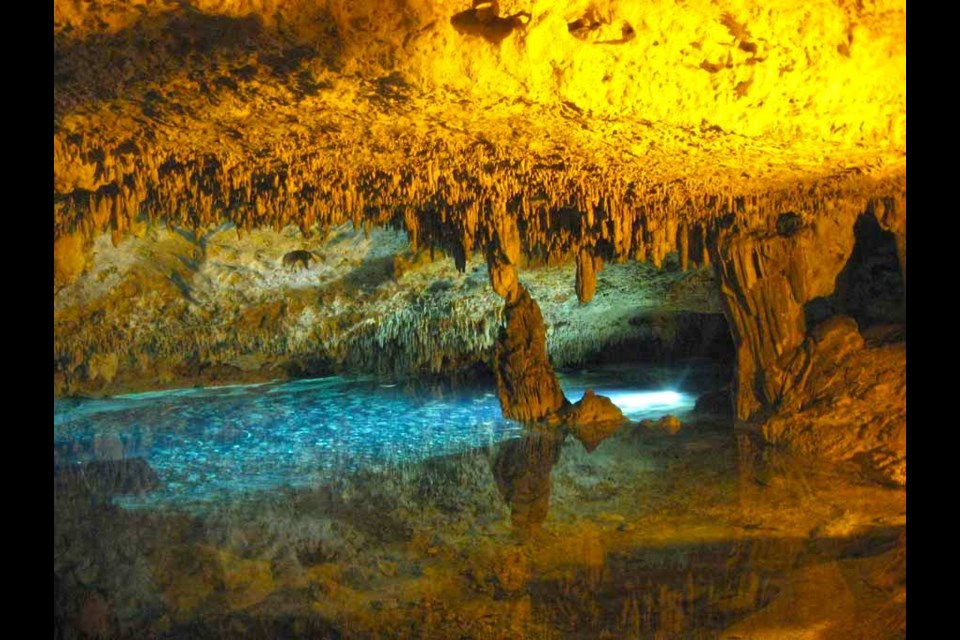 Fixed lights cast golden and aqua glows on the passages of Rio Secreto's semi-sunken cenote inside Mexico's Yucatan peninsula. Photo by Lynn Martel