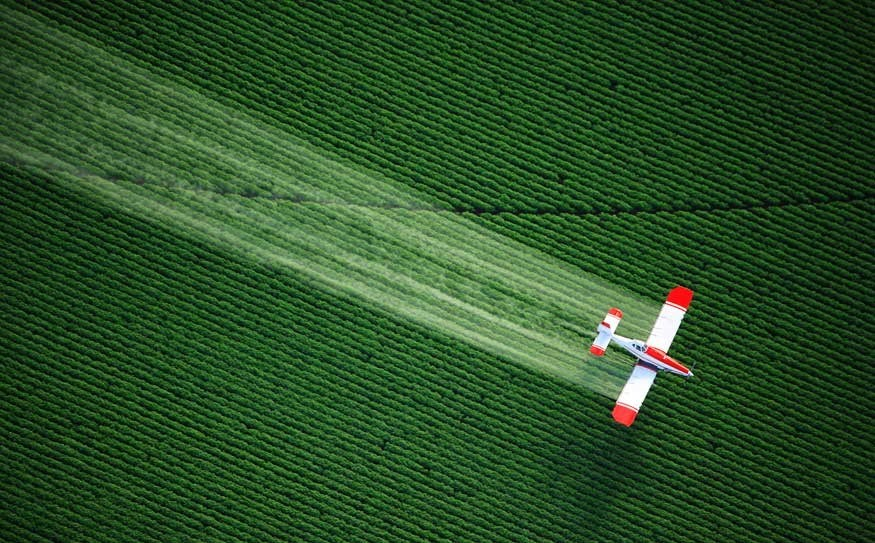 An aerial view of a crop duster spraying (usually fertilizers, pesticides, and/or fungicides), while flying low over a large agricultural farm's fields.
