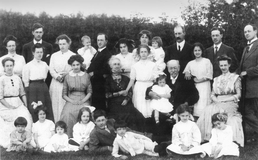 Douglas family picture 1911. In this Douglas family picture, John Barker's mother is the one-year-old seated on the ground on the left next to her sister, Margaret, with the bow in her hair — third from the left on the bottom row;