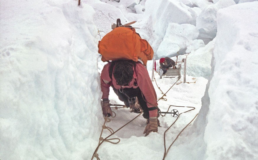 An expedition member climbs up a ladder in the Khumbu Icefall. Photo by Henry S. Hall