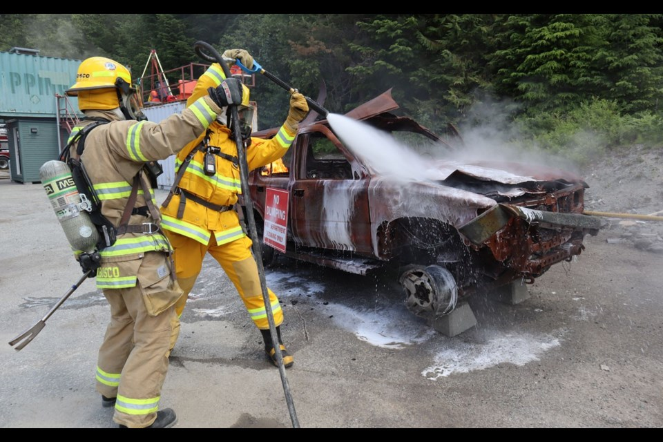 BLAZING HOT Pique reporter Braden Dupuis puts out a car fire. <ParaStyle:CUTLINE\:CUTLINE Credit>Photo by Megan Lalonde