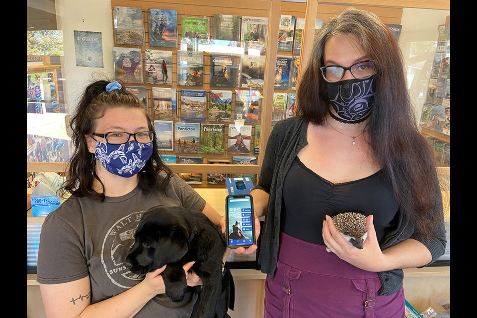 PRICKLES APPROVED: Tourism Powell River staff Melanie Ananka [left, with Jaxx] and Emily Fahey (right, with Powtown Prickles] want everyone to download the new Powell River app. The new app will have up-to-date information for visitors, residents and those who would like to become residents.