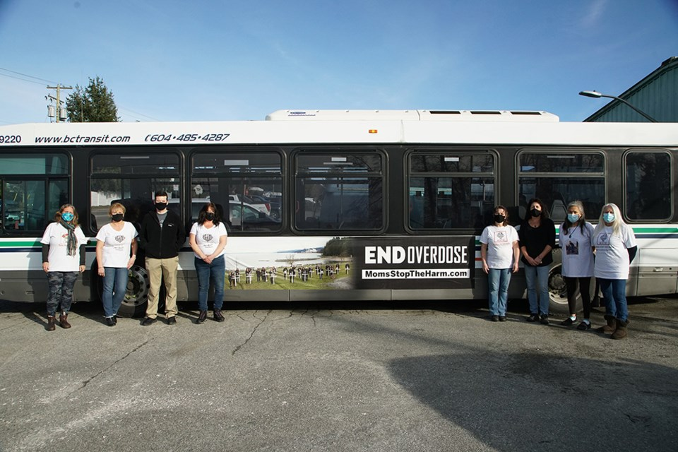 SOMBRE REMINDER: Members of Moms Stop the Harm [from left] Margo Peterson, Lyn Nicol, Rob Fitzpatrick, Darlana Treloar, Maureen Christensen, Marci Hayes, Maggy Gisle and Shirley Gentner gathered by a City of Powell River transit bus fitted with a sign that carries an important message recognizing those who have been affected by substance use overdose and the opioid crisis. Powell River's Community Action Team paid for placement of the sign, which is designed to create awareness about overdose and substance use.