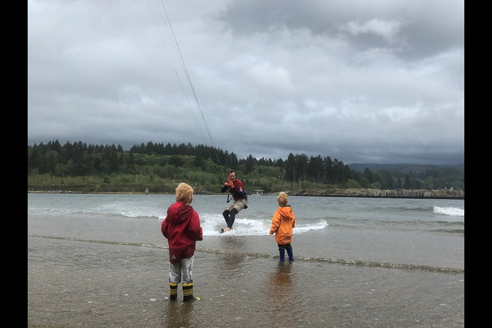 CRUISE CONTROL: Jacob Hanson takes advantage of windy conditions to return to shore at Brew Bay, south of Powell River, where his sons Hunter and Sawyer await.