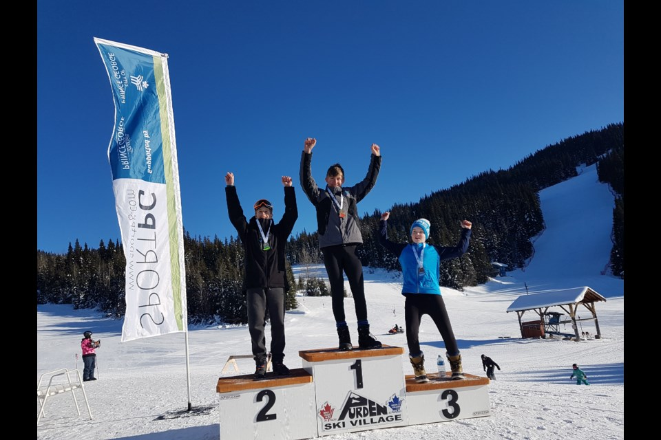 Isaac Hausot (middle) raises his hands in celebration after winning gold for the Prince George Alpine Ski Club at the 2019 TECK North Zone regionals at Purden Ski Hill (via Handout photo)