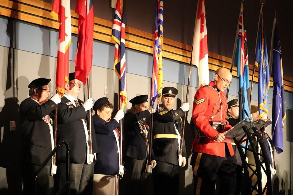 Cpl. Craig Douglass speaks in front of the Colour Guard. (via Hanna Petersen)