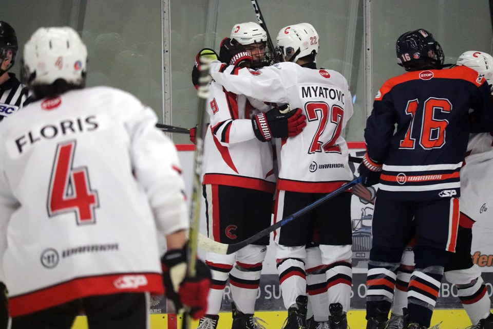 Alex Ochitwa (#8) is embraced by Nico Myatovic (#22) after scoring a goal for the Cariboo Cougars against the Thompson Blazers (via Kyle Balzer)