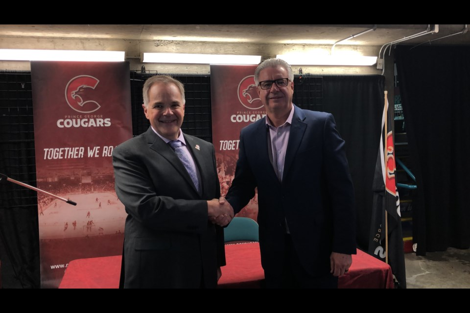 Prince George Cougars' VP of Business Andy Beesley (left) shakes hands with Mayor Lyn Hall after signing a six-year CN Centre rental renewal on June 6, 2019. (via Kyle Balzer, PrinceGeorgeMatters)