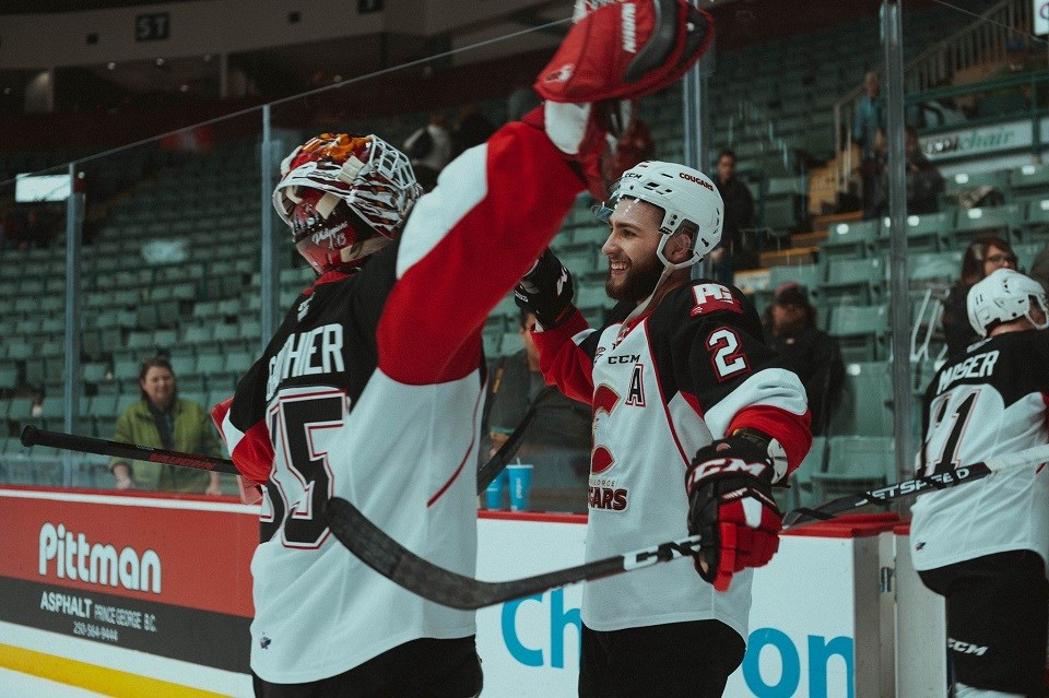 Prince George Cougars' Taylor Gauthier and Cole Moberg hug it out after beating the Seattle Thunderbirds in a shootout at the CN Centre (via Brett Cullen Photography)