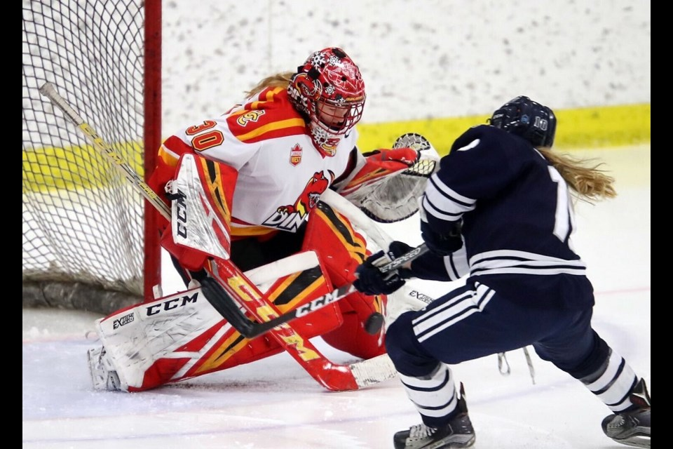 Former Northern Capitals' goaltender Kelsey Roberts (#30) makes a save for the Calgary Dinos against Mount Royal in Canada West hockey action. (via University of Calgary Athletics)