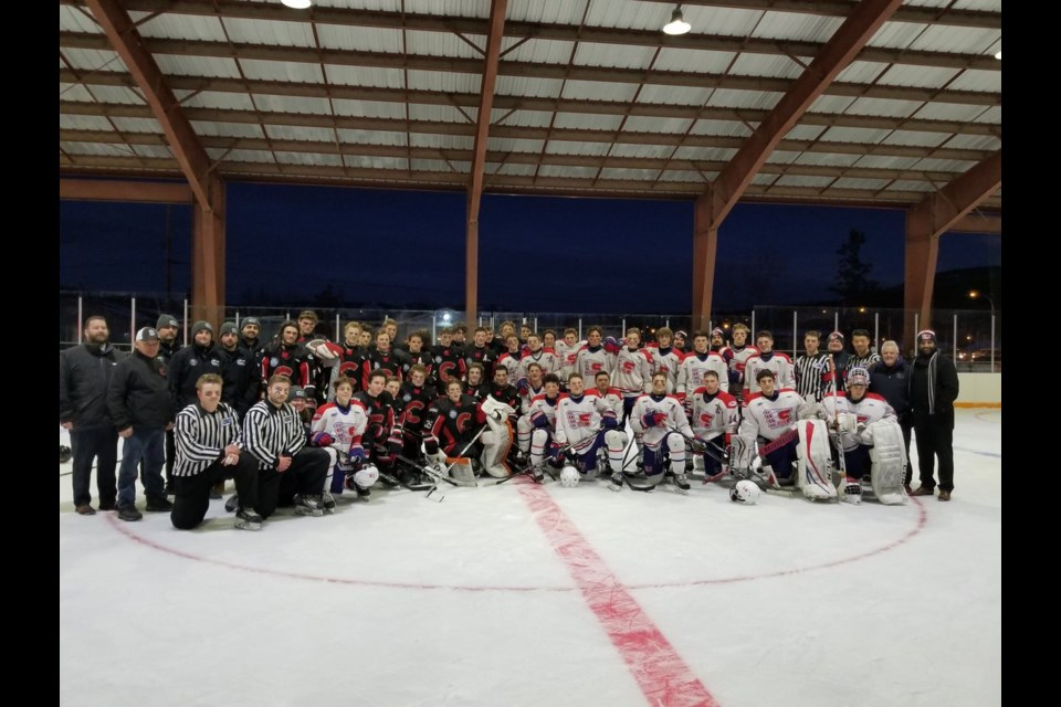 The Cariboo Cougars and Vancouver Northeast Chiefs pose for a photo after the first-ever outdoor major midget hockey game in Fort St. James (via Twitter/Nak'azdli Whut'en)