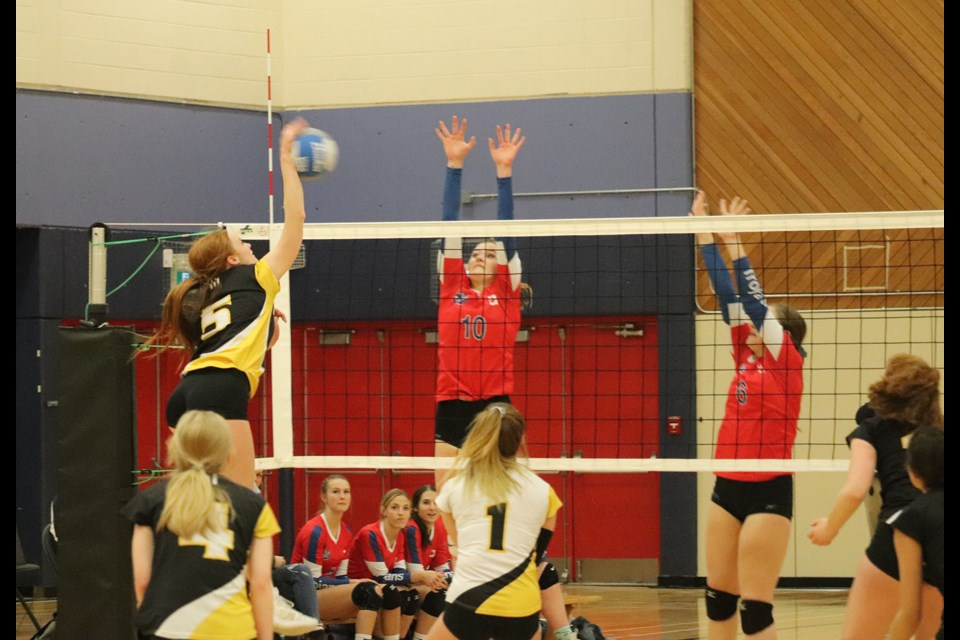 Duchess Park's Macyn Unger (#5) goes for the kill with D.P. Todd's Syerra Ferguson (#10) gets ready to block in the 2019 Prince George senior girls volleyball city championship. (via Kyle Balzer, PrinceGeorgeMatters)