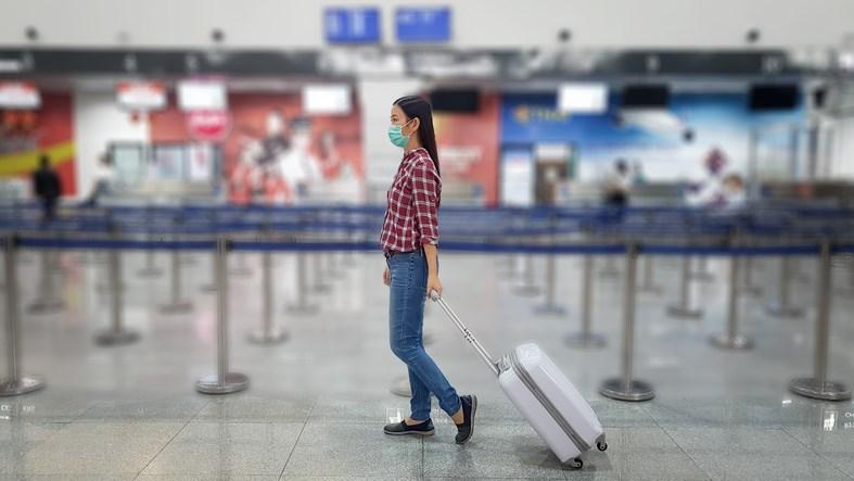A masked-up air traveller walks through an empty airport.