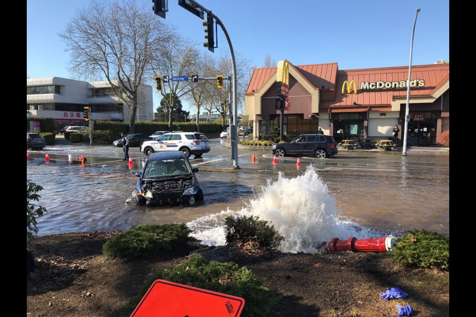 A car appears to have hit a fire hydrant in Richmond City Centre, causing water to flood into the intersection.