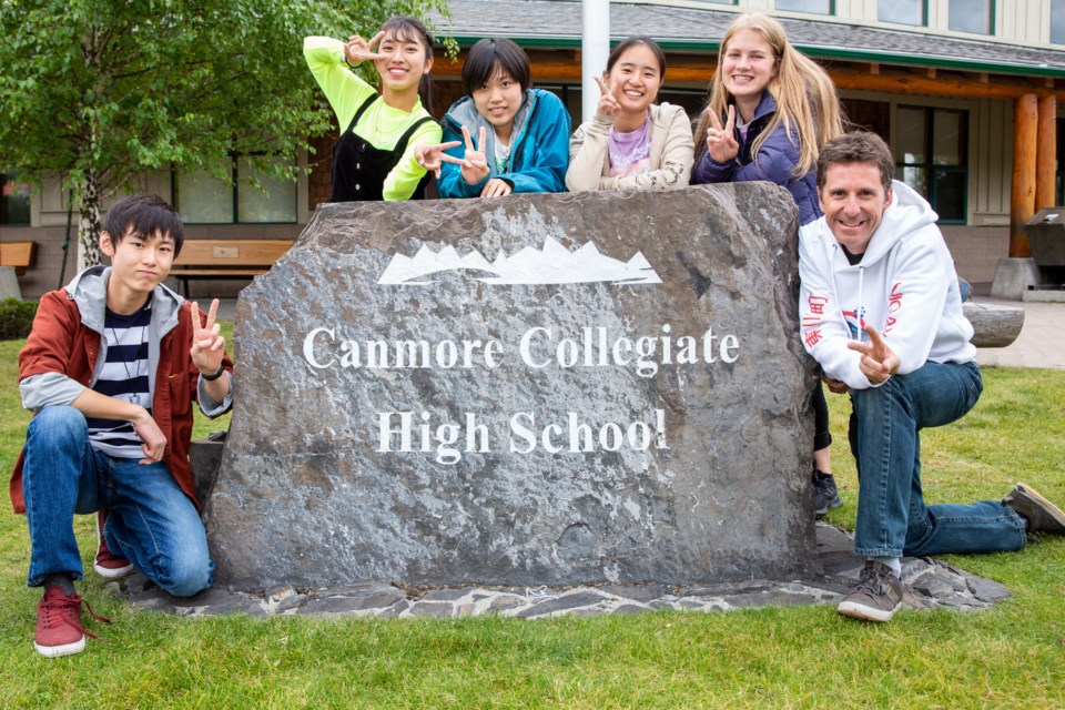Japanese exchange students Shunshuke Nishimura, left, Karen Ishikawa, Amane Habuki,  Mikoto Okazaki, Canomore Colligate student Anika Gasser and teacher Ken Symington pose in front of the Canmore Colligate High School on Sept. 18. The four exchange students, who are from Higashikawa, Canmore'™s sister-city in Japan, spent two weeks in the Bow Valley. Evan Buhler RMO PHOTO