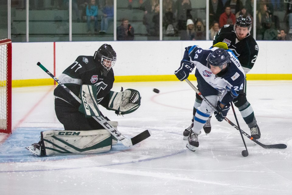 The Sherwood Park Crusaders goaltender Carter Gylander makes a save as the Eagles Michael Spafford is checked by the Crusaders Max Wutzke during a game at the Fenlands Banff Recreation Centre on Friday (Oct. 4). Evan Buhler RMO PHOTO