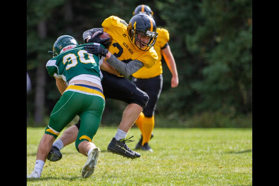 Canmore's Eric Kania makes a tackle against the Olds running back during a game at Millennium Park on Saturday (Oct. 5). Evan Buhler RMO PHOTO