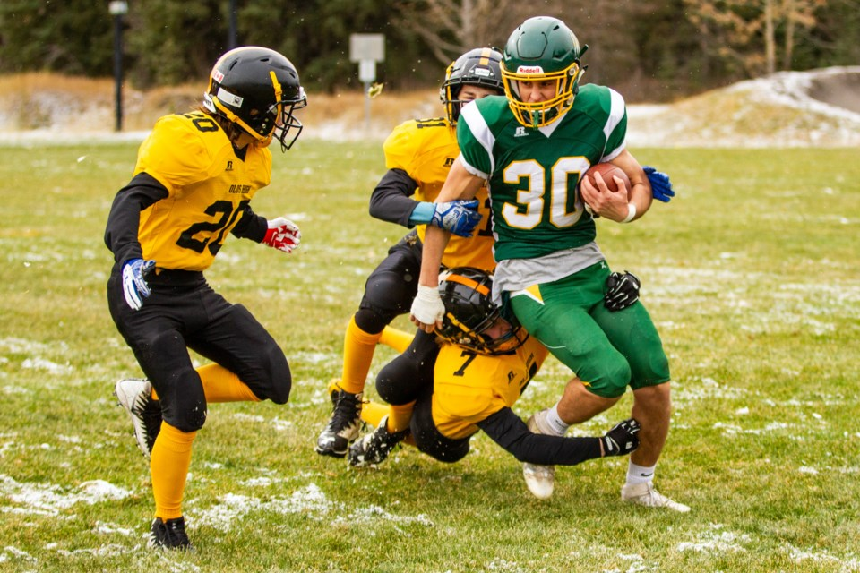 The Wolverines Eric Kania is hauled down by two Olds linebackers during a first round playoff game at Millennium Park on Saturday (Oct.26). Evan Buhler RMO PHOTO