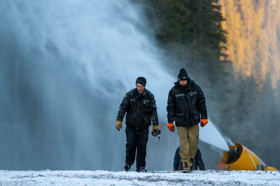 "Mt. Norquay snow makers, Arnaud Bourdon, left, and Mike ""Radar"" Rae walk near a large snow gun before the opening day of the 2019 season at Mt. Norquay. RMO FILE PHOTO"