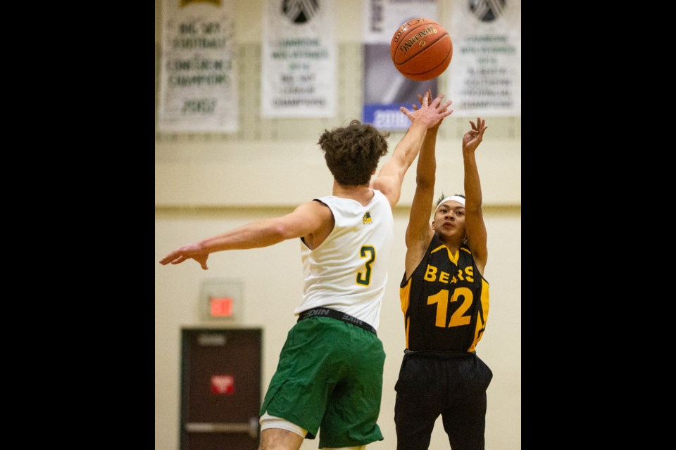 Ryan Brunet of Canmore attempts to block a shot by Banff's Jaden Samson in the first game of Canmore Collegiate High School's annual basketball tournament on Friday (Dec. 6). EVAN BUHLER RMO PHOTO⁠