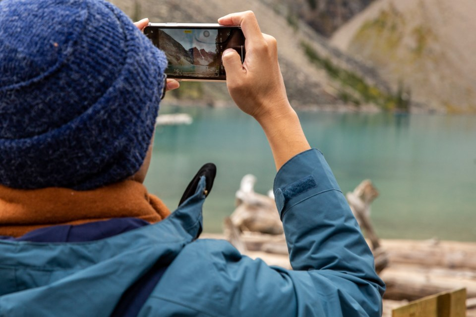 A tourist takes a picture of Moraine Lake with his mobile phone on Saturday, September 14, 2019. The parking lot at Moraine Lake was closed at 6 a.m. as hundreds of tourists flocked to the lake.